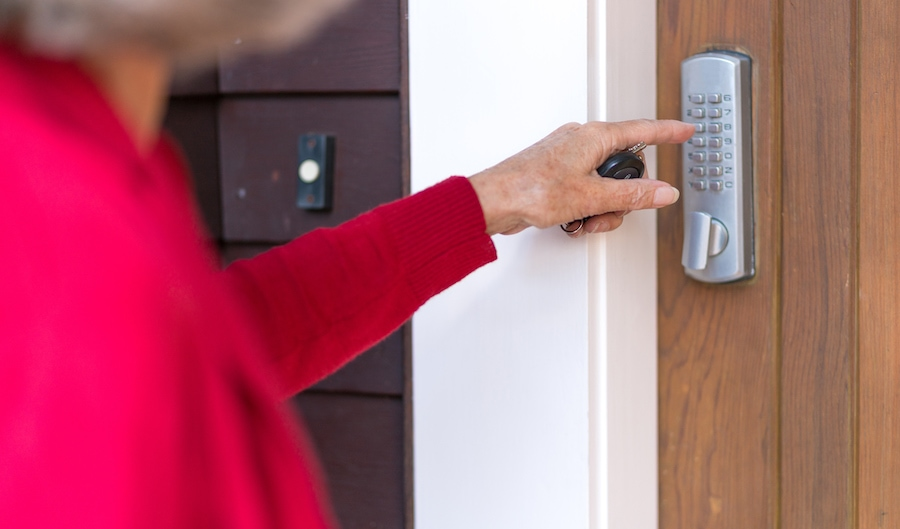 Senior woman uses keypad on digital lock to unlock and open domestic front door. The Future of Locksmithing: No More Keys.